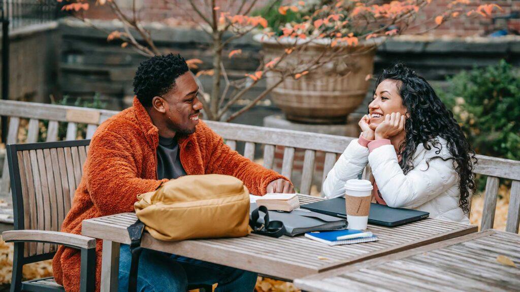 due ragazzi che si sorridono seduti ad un tavolino all'aperto